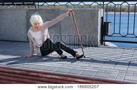 Do not be indifferent. Humble upset confused woman using a stick and lifting on the toes while falling down
