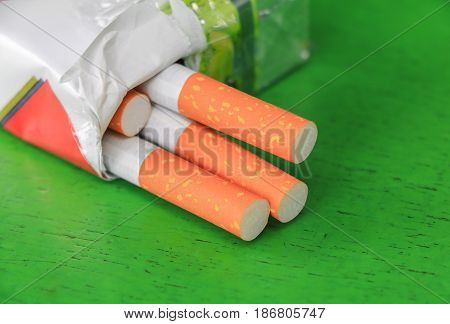 closeup cigarette in the package on the green wood table. concept Non-smoking day universal