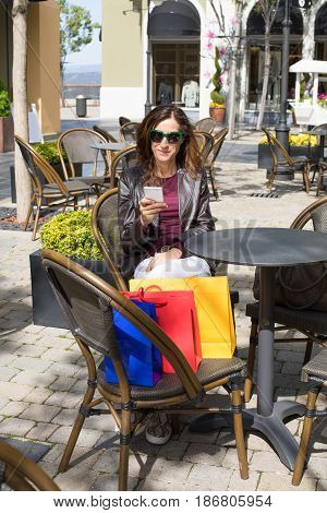 Woman Sitting In Cafe Terrace With Shopping Bags Using Phone