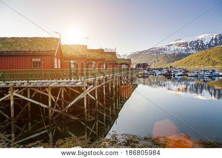 Red wooden cabins at campsite by the fjord in Norway