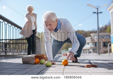 Pain can kill us. Weak startled senior man feeling sickness and dropping fruits while kind woman looking at him