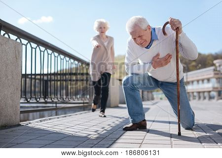 Harsh reality of retirement. Feeble hopeless aged man having pain and holding his hand on the chest while not indifferent woman dashing to help him