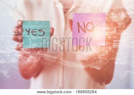 Illuminated cityscape against mid section of businesswoman showing yes and no cards