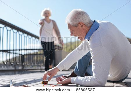 Necessary aid giving behavior. Sick old sad man falling on his way letting drop his medicine while great woman wending her way to him