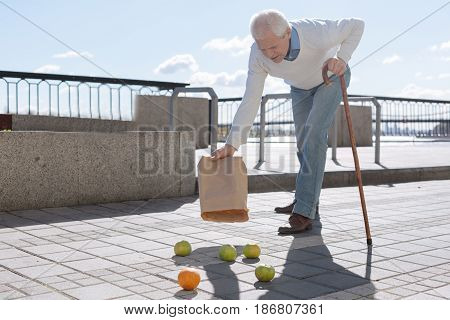 Take care. Good clever tired man taking the stick in one hand dropping and emptying fruits on the ground