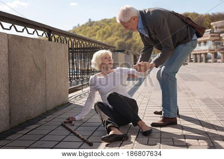 Elderly assisted by elderly. Aged pleasant kind woman falling and leaving go her stick while gentle man raising her up