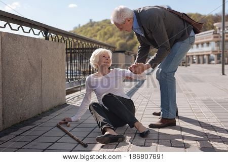 Always rescue each other. Old pretty cheerful woman lying on the ground and smiling while polite husband helping her