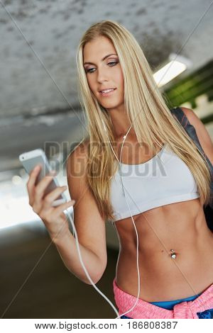 Pretty blonde fit girl using mobilephone, walking in tunnel.