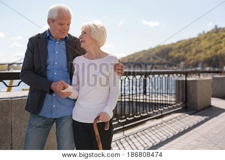 Enjoying great time together. Lovely wonderful happy couple smiling and discussing their lives while going along the promenade