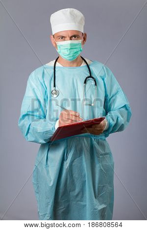 Medical Doctor With Stethoscope And Face Mask Holding A Pen And Writing In A Notebook. Grey Backgrou