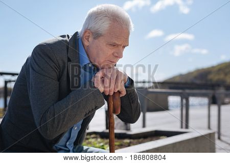 Memory crushing us. Calm sullen sad man crossing hands on the stick and feeling upset while looking down and thinking