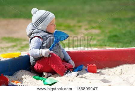 Portrait of toddler child wearing vest jacket outdoors. One year old baby boy playing with sand at playground sandbox