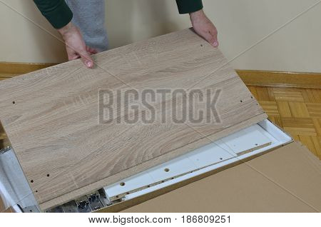 Man Unpacking Elements Of Cabinet