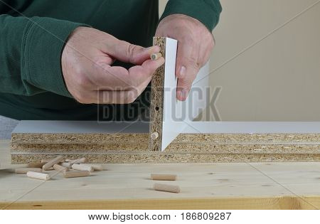 Man inserting wooden dowels into a particle board of a new piece of furniture