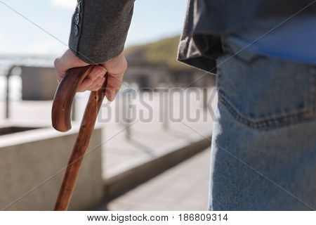 Reliable support for pensioners. Ordinary calm senior man using special tool while walking and having problems with feet
