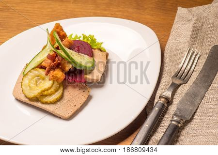 Danish specialties and national dishes high-quality open sandwich Liver Pate with bacon pickled cucumber beetroot and cucumber served on a plate ready for eating