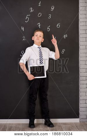 Handsome School Boy In Googles White Shirt Tie Standing Close To School Desk With Numbers Above Arou