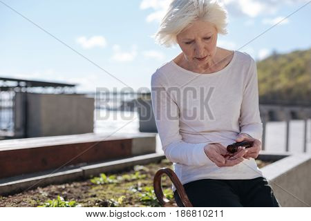 Viruses around us. Beautiful upset senior pensioner sitting and recalculating pills in the street while feeling tranquility