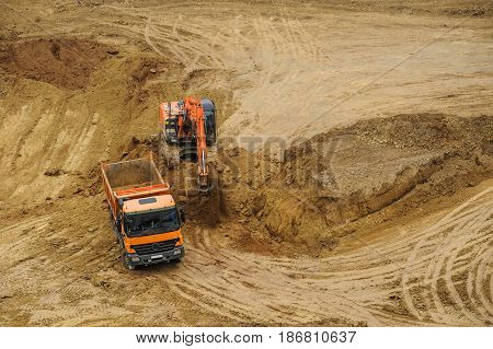 Excavator Moving Earth And Unloading Into A Dumper Truck