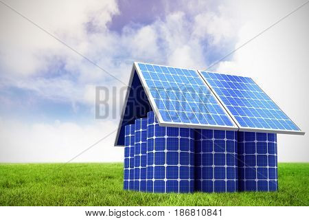 3d image of model home made from solar panels and cells against blue sky over green field