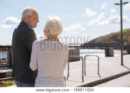 Love you forever. Happy senior gentle man feeling happiness while resting and discussing day with his wife