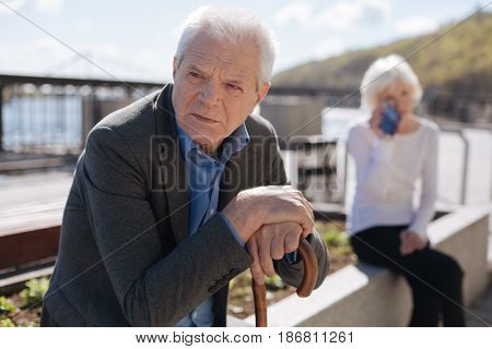 Mulling over the future. Aged puzzled san pensioner his hands on the stick and looking far ahead while unhappy woman feeling depressed