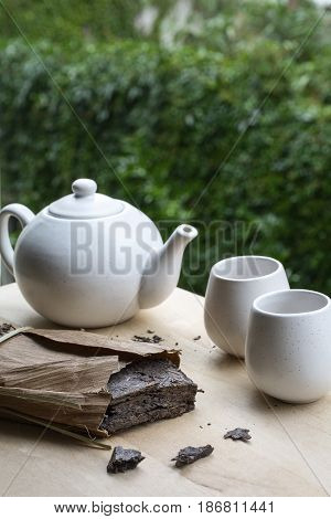 One pack of black natural tea with white teakettle and two cups with green leaves as background