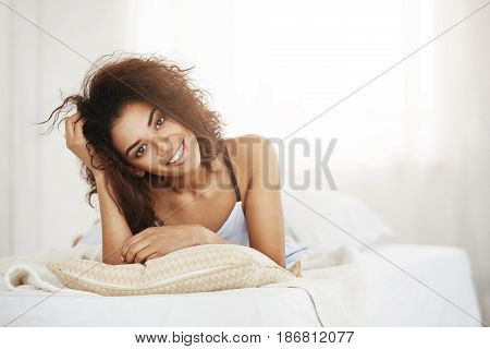 Beautiful happy african girl lying on pillow at home early in morning smiling looking at camera.