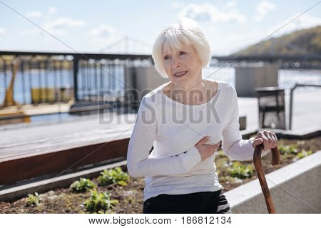 Signals from your body. Good-looking unhappy ill woman suffering from heart attack while sitting on the bench and waiting for husband