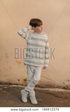 little boy in white jeans and sweater posing on the street at the wall