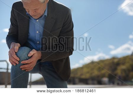 Unbearable pain in my body. Old pleasant involved man touching his knee and suffering from pain while walking outdoors