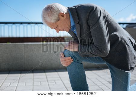Feeling bad symptoms again. Retired stylish ill man touching his knee and expressing discontent while walking in the open air