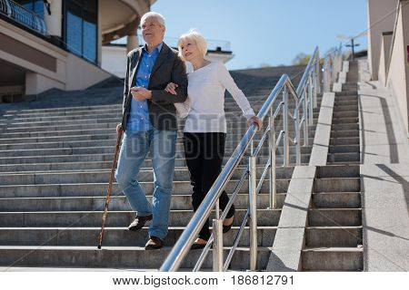 Looking with hope in future. Happy wonderful pleasant couple scrutinizing the horizon and smiling while going downstairs