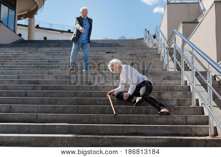 Help each other. Scared upset sick woman falling on the stairs and exposing cramp while aged man hurrying to her