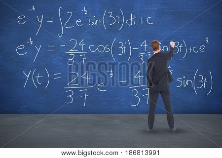 Rear view businessman writing with chalk against blue room