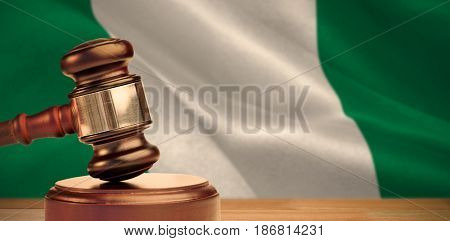 Hammer and gavel against 3d digitally generated nigerian national flag