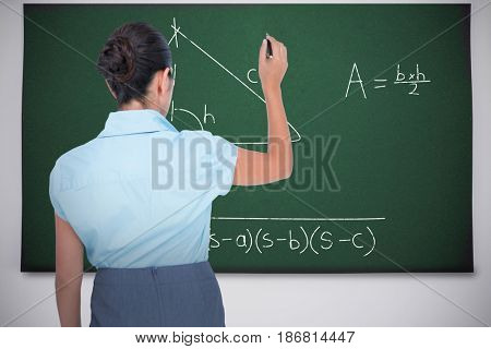 concentrated businessman writing with marker against black chalkboard