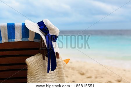 hat and bag with suncream on tropical beach vacation