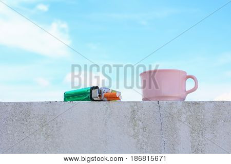 coffee cup pink and a cigarette pack lighter on the floor. with blue sky background concept Non-smoking day universal