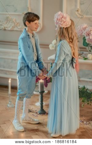 little boy and girl in the blue dress in the Studio with flowers and candle