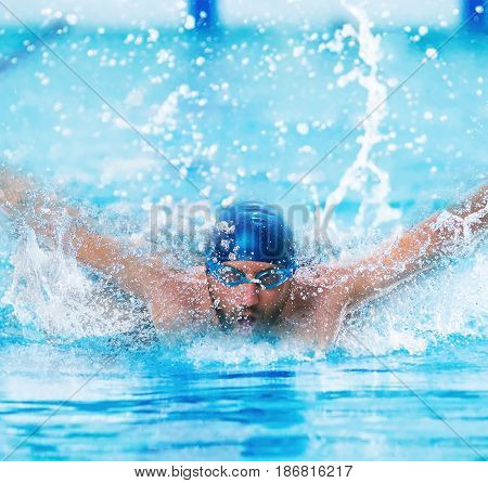 The dynamic and fit swimmer in cap breathing performing the butterfly stroke