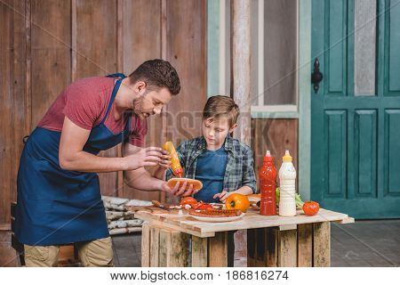 Cute Little Boy With Father In Apron Preparing Hot Dog Together In Backyard, Dad And Son Cooking Con