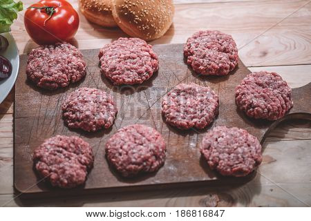 Top View Of Raw Meat Patties For Burgers On Wooden Cutting Board
