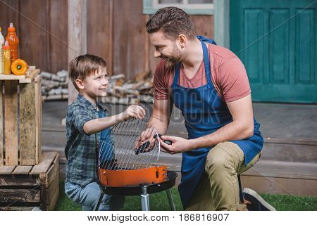 Side View Of Smiling Father And Son Preparing Grill For Barbecue