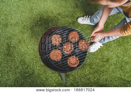 Partial View Of Boy Cooking Meat Patties On Grill