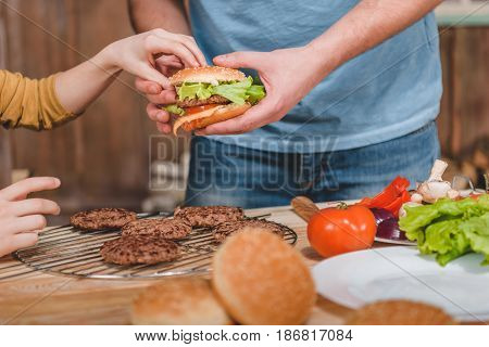 Partial View Of Dad And Son Cooking Meat Burgers Together