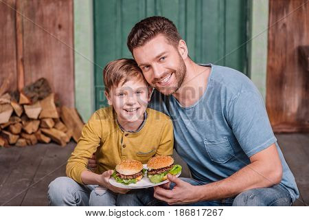 Portrait Of Happy Father And Son Holding Plate With Homemade Burgers