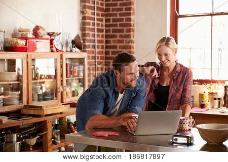 Young couple using laptop computer in kitchen, high angle