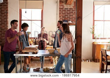 Friends talking over coffee in kitchen, three quarter length