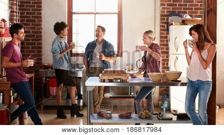 Five friends stand hanging out in kitchen, quarter length